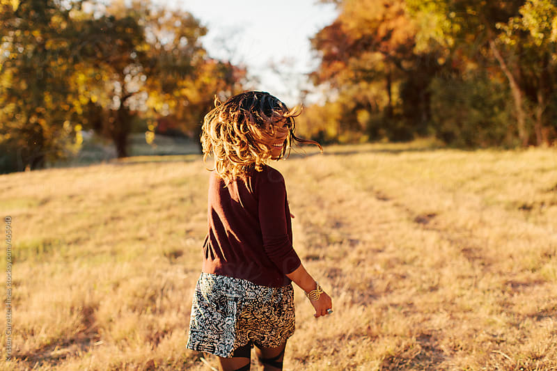 Young care free woman running through an open field.  by Kristen Curette Hines for Stocksy United