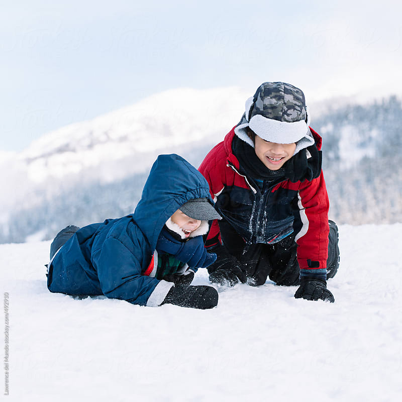 Two kids having fun and playing in the snow  by Lawrence del Mundo for Stocksy United