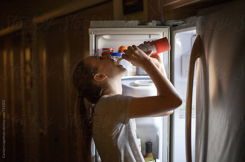 Teenage girl standing at the refrigerator spraying whip cream into her mouth by Carolyn Lagattuta for Stocksy United