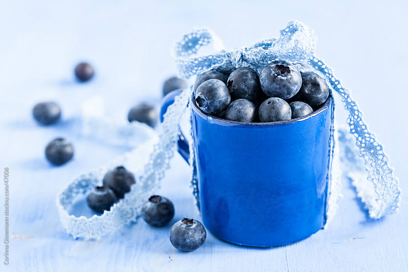 fresh blueberries in a cup with ribbon on blue background by Corinna Gissemann for Stocksy United