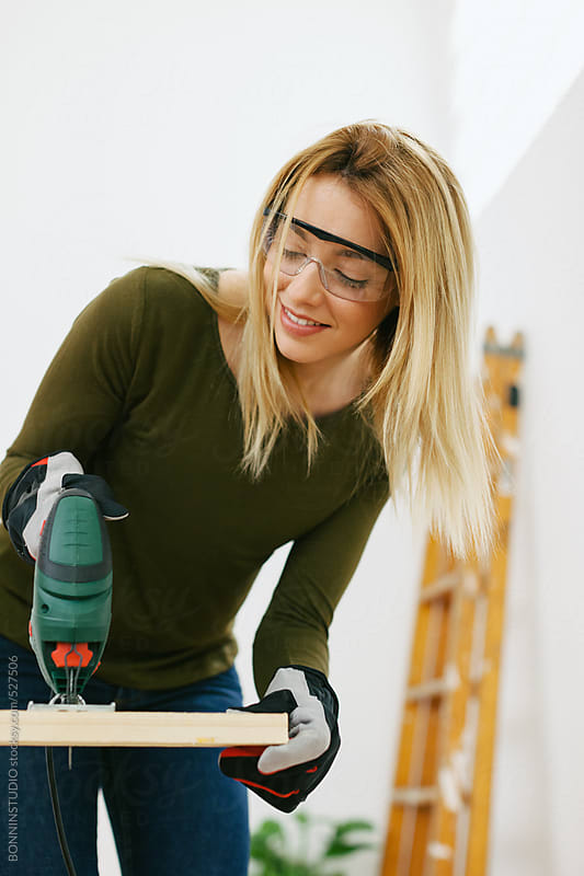 Young woman cutting wood plank with a saw.  by BONNINSTUDIO for Stocksy United