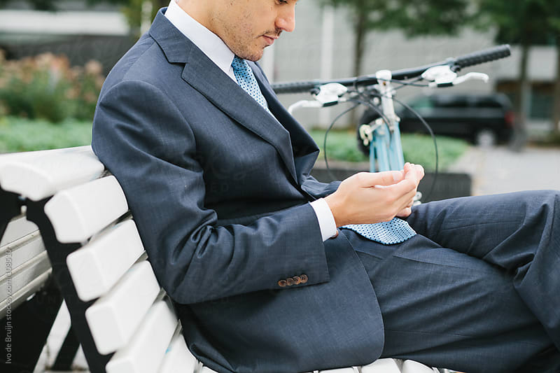 Well dressed business man in suit using his cellphone after cycl by Ivo de Bruijn for Stocksy United