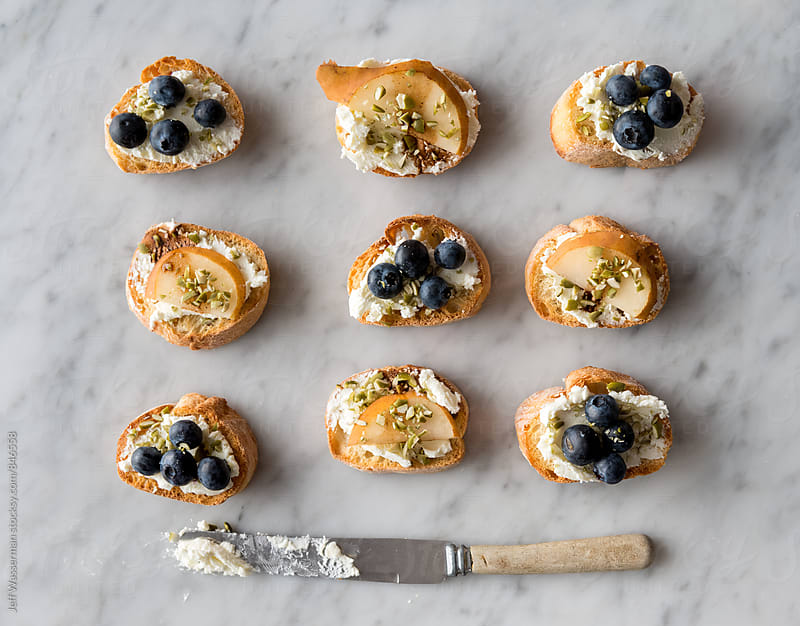 Crostini with Goats Cheese, Pear and Blueberry From Above by Jeff Wasserman for Stocksy United