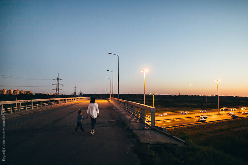 Mother and boy cross the bridge at night by Evgenij Yulkin for Stocksy United