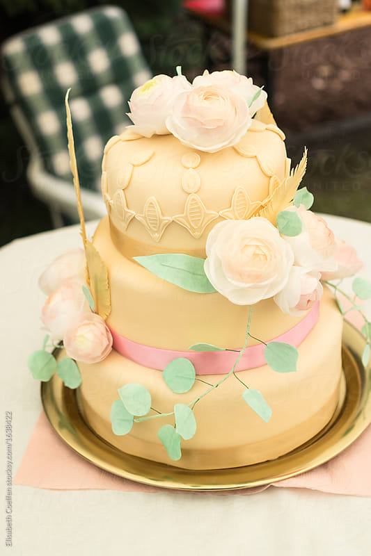 Three tiered wedding cake with fondant and ranunculus flowers ...