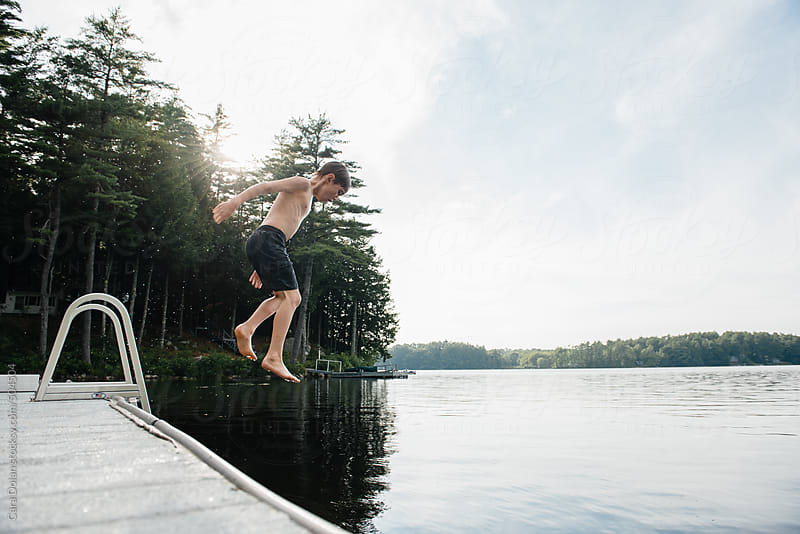 Child jumps into lake water from dock by Cara Dolan for Stocksy United