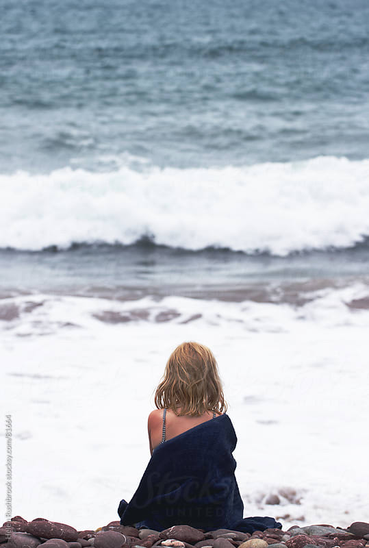 A little girl wrapped in a towel sitting on the shore. by Helen Rushbrook for Stocksy United