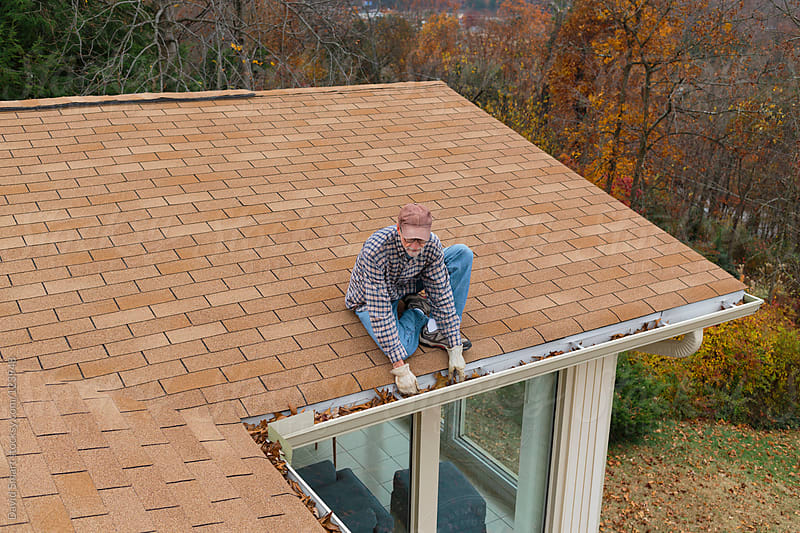 Man cleaning gutters on a house by David Smart for Stocksy United