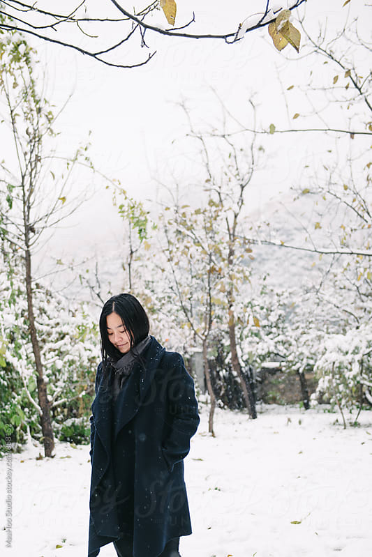 Woman standing in snowy courtyard by Maa Hoo for Stocksy United