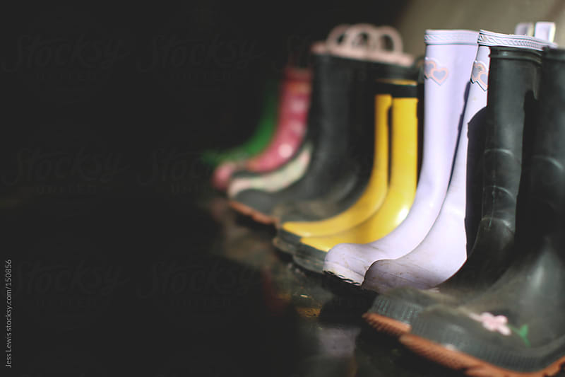 rain boots lined up along wall by Jess Lewis for Stocksy United