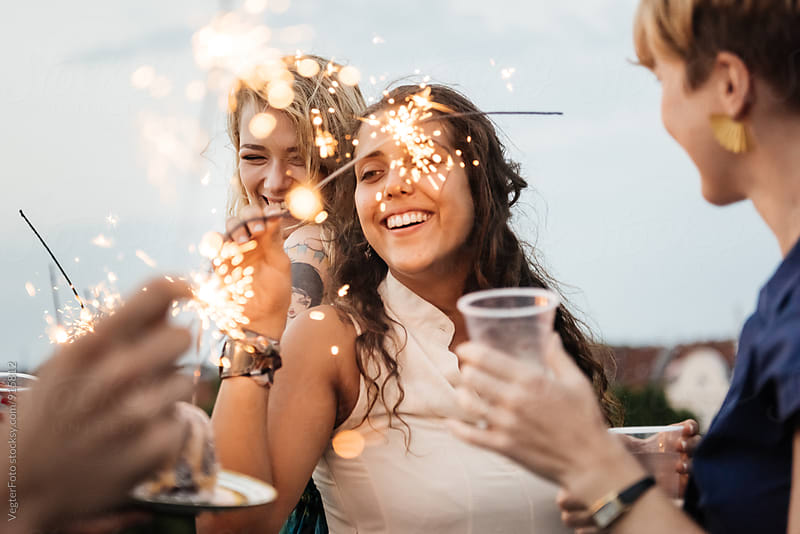 Young women having fun on a rooftop with sparklers. by VegterFoto for Stocksy United