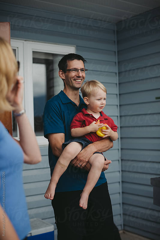 Man smiling and holding toddler boy near house by Rob and Julia Campbell for Stocksy United