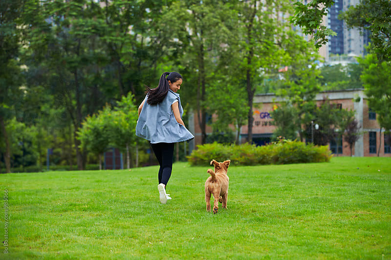 happy young asian woman with her dog in the park by Bo Bo for Stocksy United