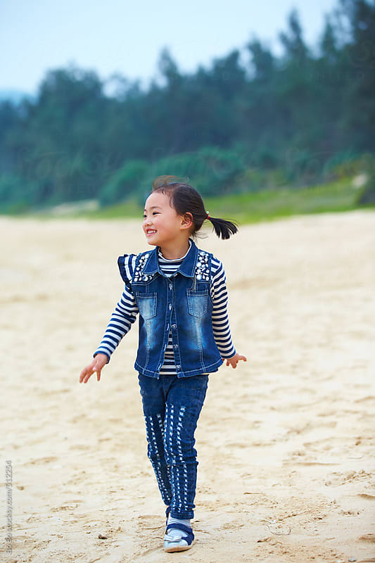 happy little asian girl playing on beach  by Bo Bo for Stocksy United