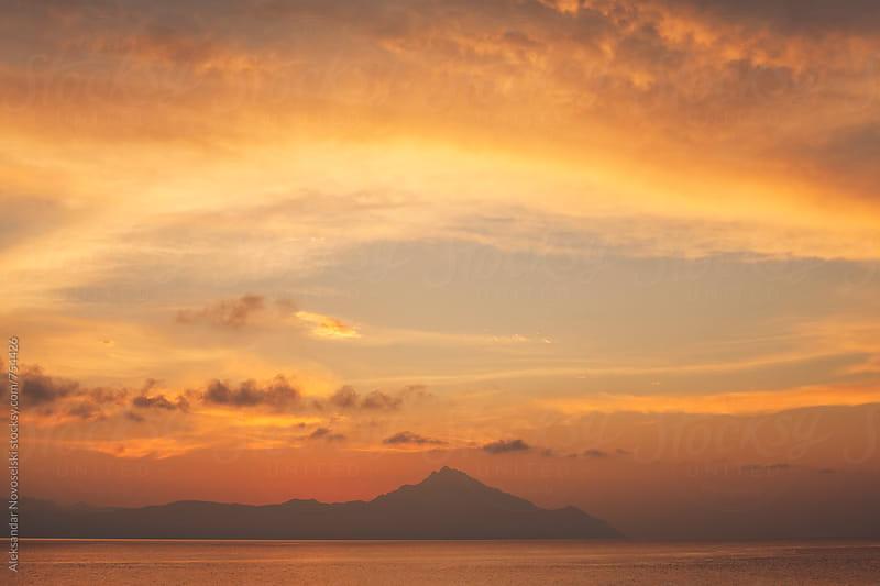 Minimalist seascape at dawn with nice clouds above Athos, Greece by Aleksandar Novoselski for Stocksy United