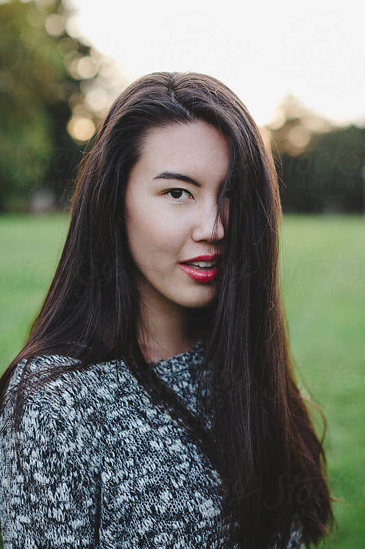 Beautiful young asian woman outside on field  by Rob and Julia Campbell for Stocksy United