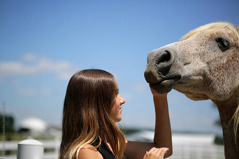 A Teen Girl Petting A Horse On A Summer Day by ALICIA BOCK for Stocksy United