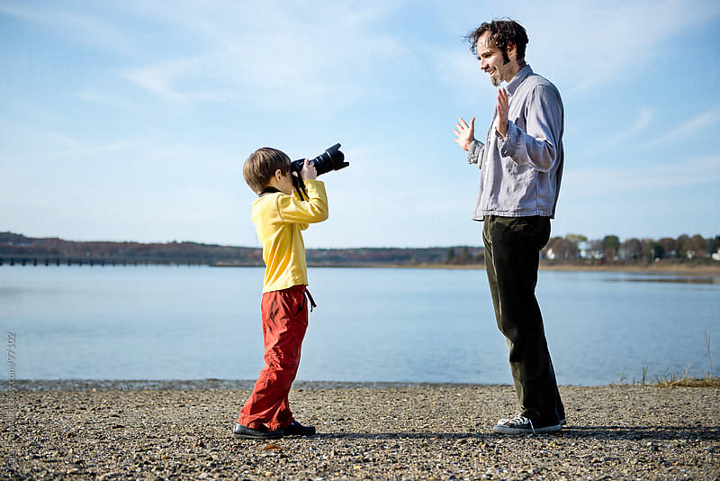 Boy on a beach takes a picture of his father with a digital SLR camera by Cara Dolan for Stocksy United
