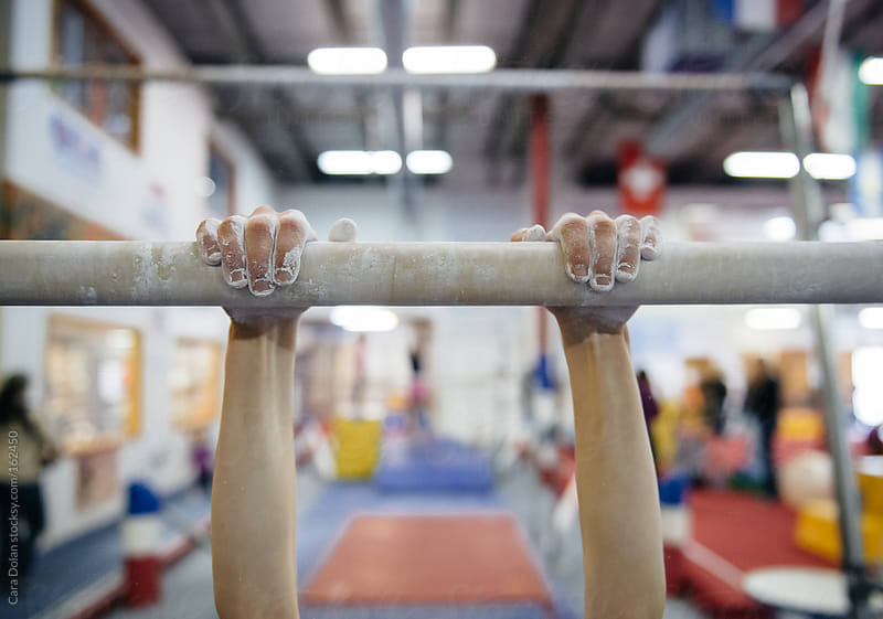 Child practices on the parallel bars in a gymnastics gym by Cara Dolan for Stocksy United