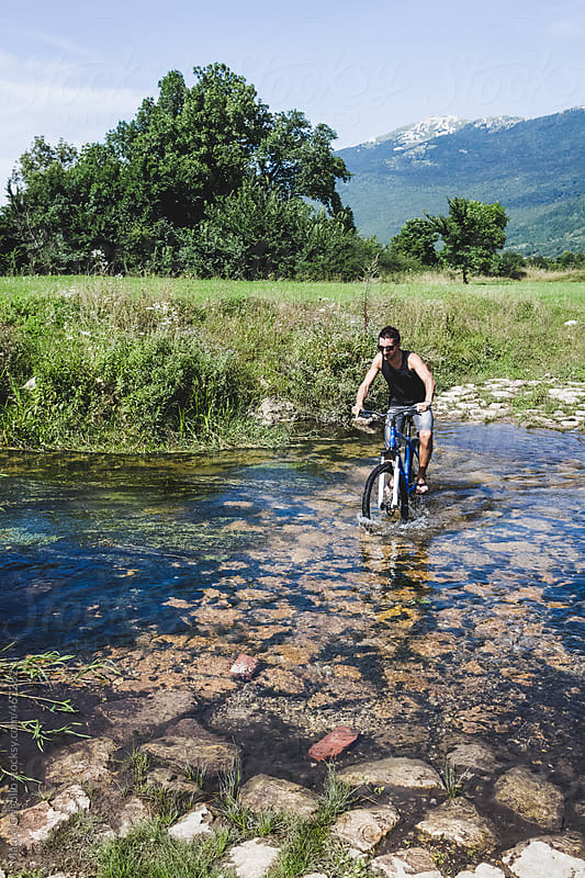 Man crossing the river with mountain bike by Mauro Grigollo for Stocksy United