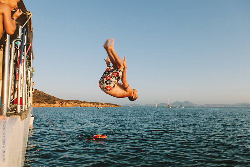 Young Man Having Fun Jumping in Water From a Boat by VICTOR TORRES for Stocksy United