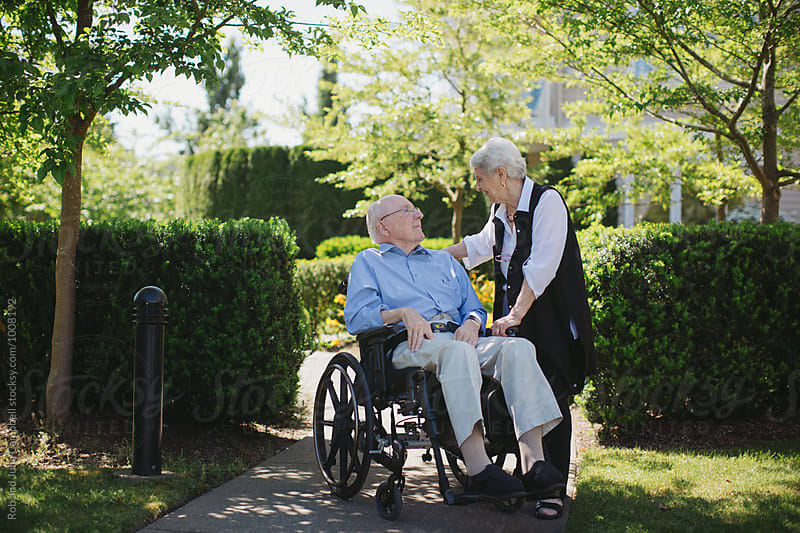 Tender moment between senior couple outside together with wheelchair by Rob and Julia Campbell for Stocksy United