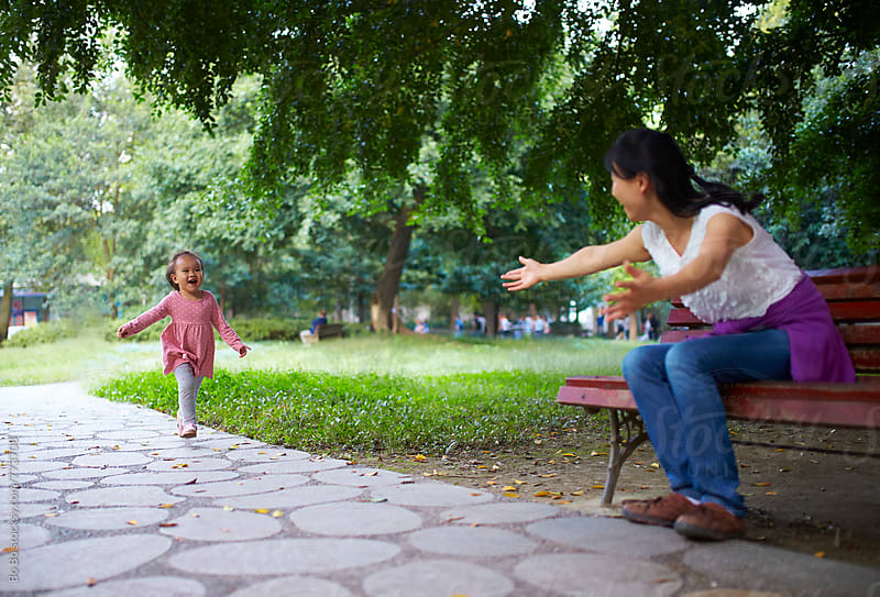 happy little girl playing with her mother in the park by cuiyan Liu for Stocksy United