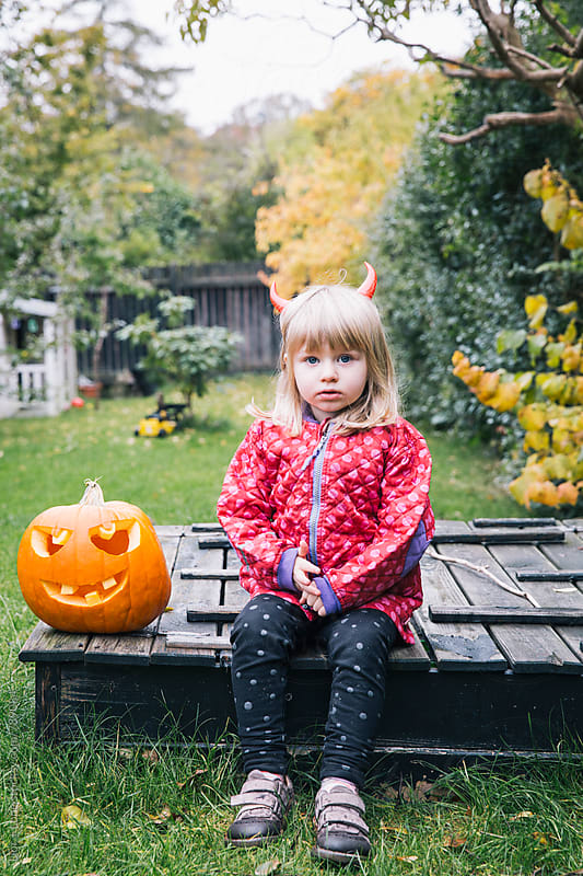 Little girl with red horns in garden at Halloween by Lior + Lone for Stocksy United
