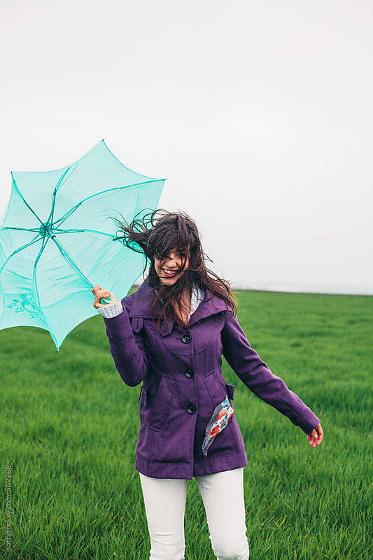 Beautiful young woman holding umbrella on a windy day by paff for Stocksy United