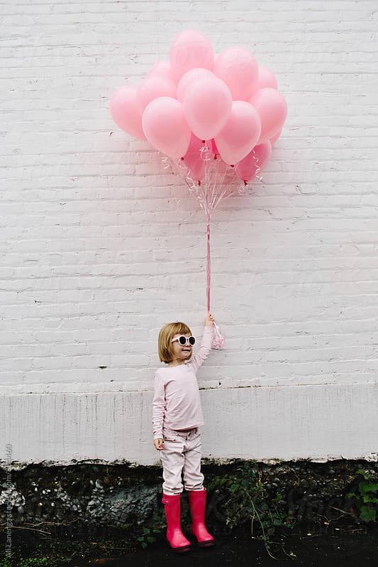 Girl holding pink balloons by Ali Lanenga for Stocksy United