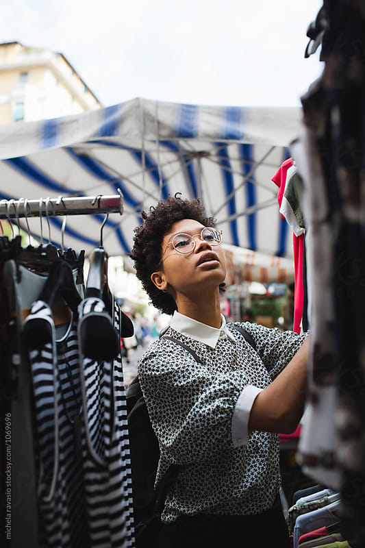Afro woman shopping for clothes by michela ravasio for Stocksy United