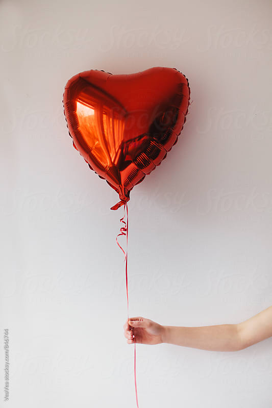 Hand holding a red heart ballon in front of a white wall by Marija Mandic for Stocksy United