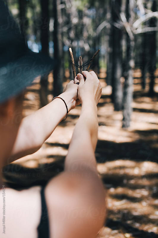 Girl in the forest playing with a tiny homemade sling shot by Jacqui Miller for Stocksy United