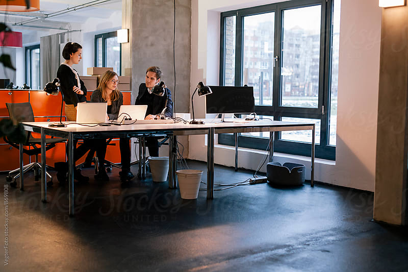 Colleagues in an informal meeting in modern office by VegterFoto for Stocksy United