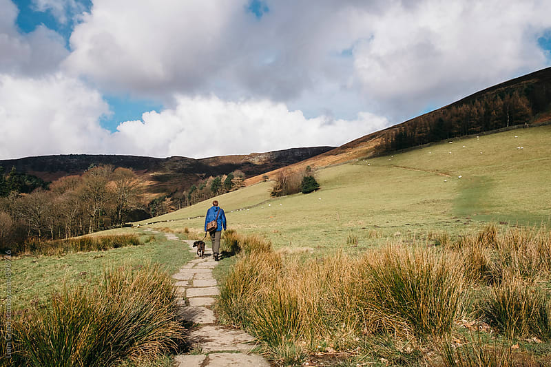 Male and his dog walking along a stone footpath. Edale, Derbyshire, UK. by Liam Grant for Stocksy United
