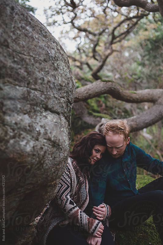 Young couple cuddling together outside in west coast nature by Rob and Julia Campbell for Stocksy United