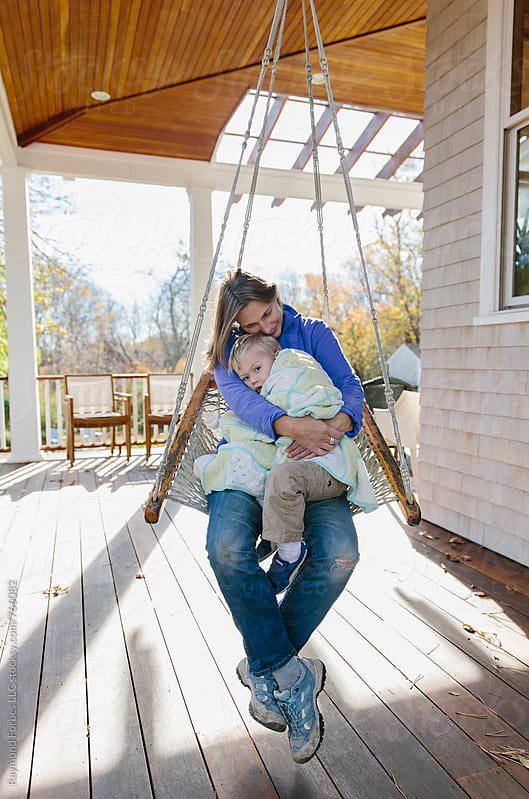 Mother Swinging on Porch on Autumn Day by Raymond Forbes LLC for Stocksy United