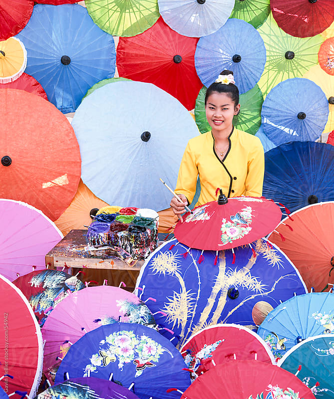 Woman painting umbrellas, Bo Sang umbrella village, Chiang Mai, northern Thailand, Asia by Gavin Hellier for Stocksy United