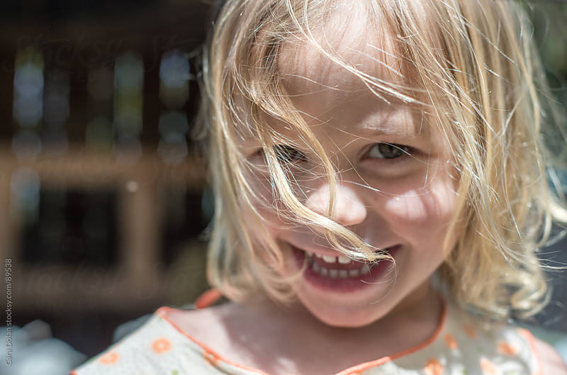 Happy little girl with hair blowing in her face by Cara Dolan for Stocksy United