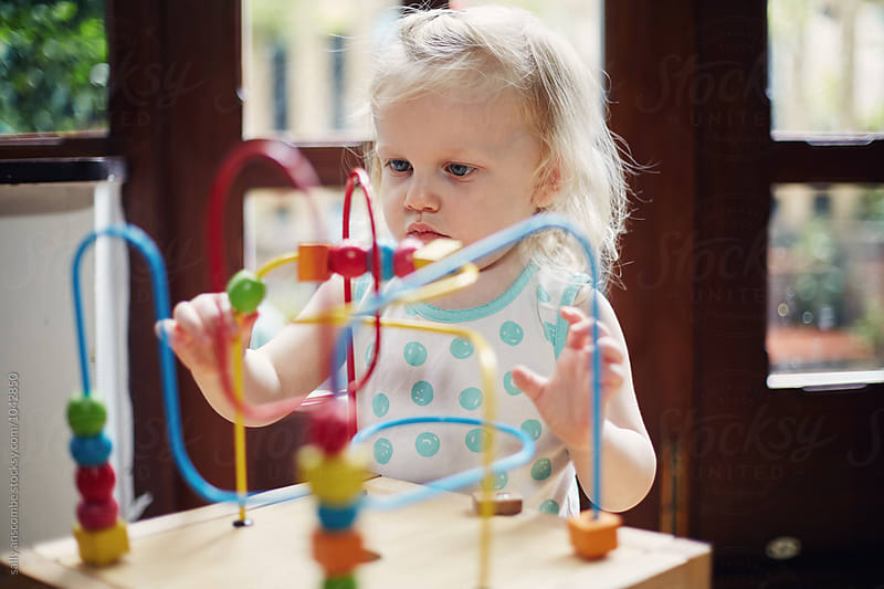 Child playing with a wooden toy by sally anscombe for Stocksy United