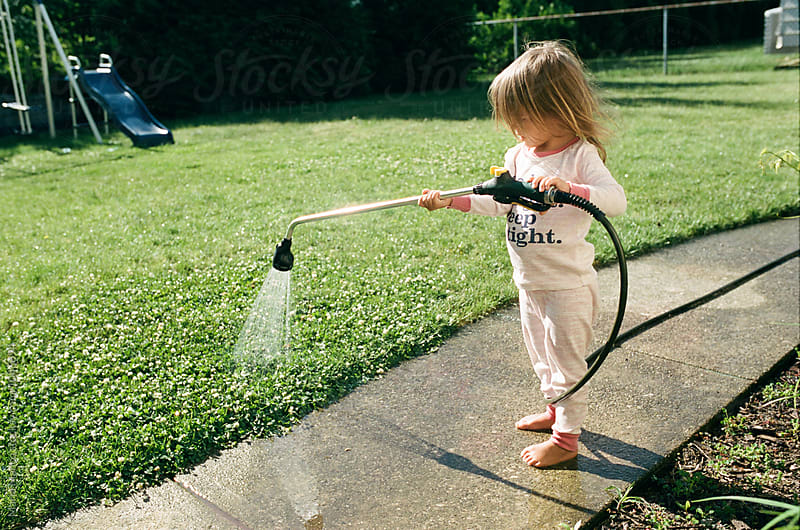 little girl sprays hose by Maria Manco for Stocksy United