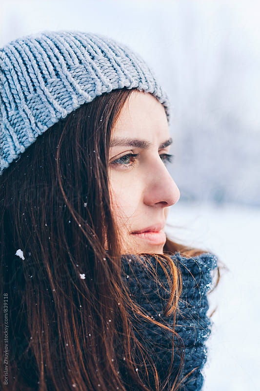 Young woman wearing knit hat in snowy field by Borislav Zhuykov for Stocksy United