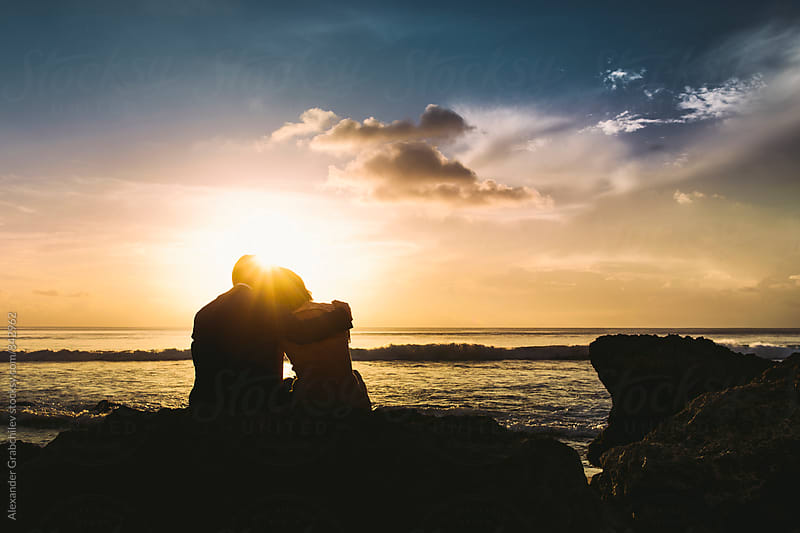 Young Couple At Sunset Beach by Alexander Grabchilev for Stocksy United