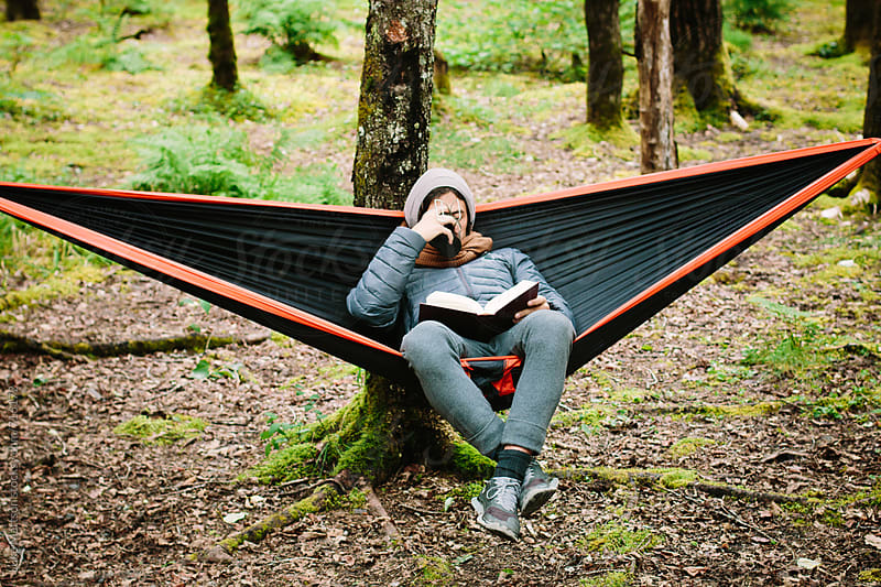Young Man Sitting In A Hammock Reading A Book And Sipping Coffee From A Canteen Cup In the Woods by Luke Mattson for Stocksy United