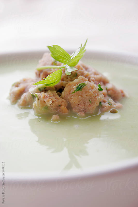 Vegetable cream soup with dumpling and herb in a bowl by Ferenc Boros for Stocksy United