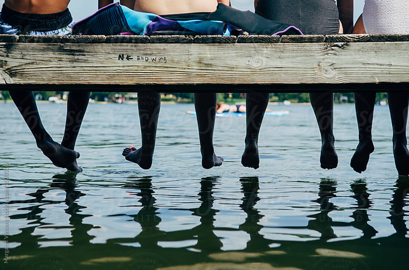 four teenagers sit at the end of a dock, legs and feet edition by Margaret Vincent for Stocksy United