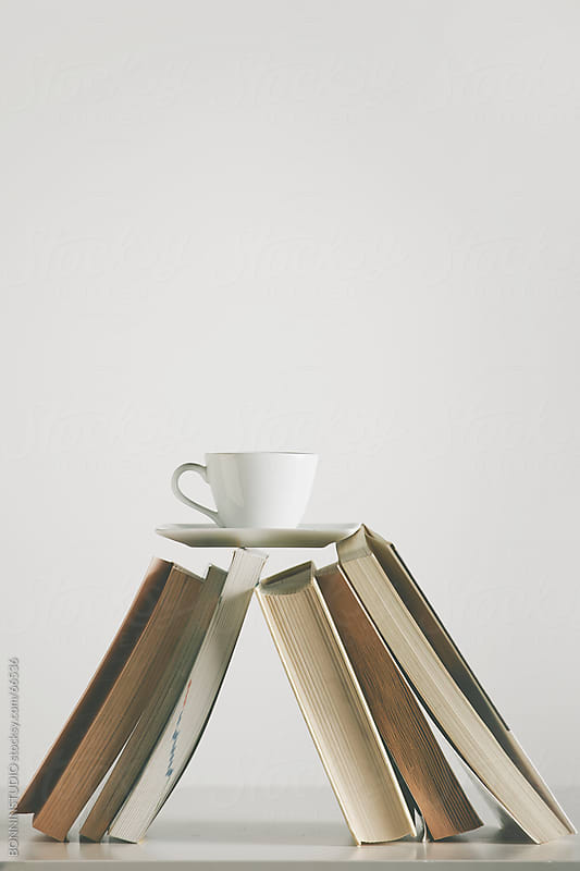 Coffee cup over a book on the table. White background. by BONNINSTUDIO for Stocksy United