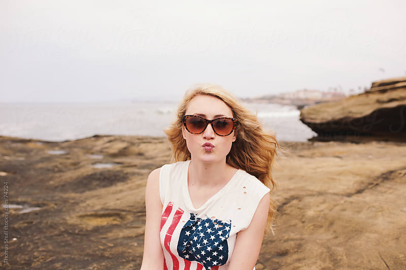 Pretty girl in American Flag Shirt at the beach by Thomas Shull for Stocksy United