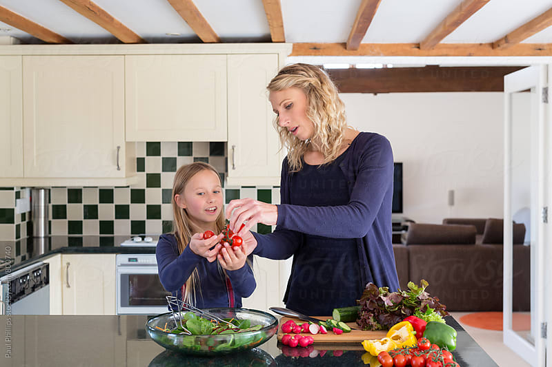 Mother and daughter preparing a salad in a kitchen by Paul Phillips for Stocksy United