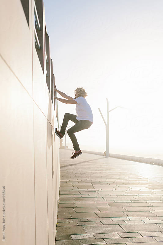 Man climbing a wall to get higher up. by Denni Van Huis for Stocksy United